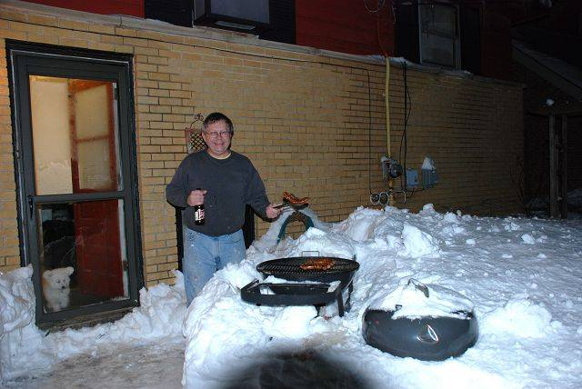 Bruce Plazyk of Wheaton grills Italian sausage on Wednesday night.