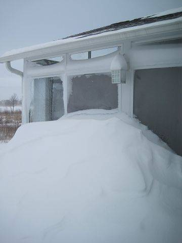 Lynne and Denny Freund's porch at Del Webb, Huntley is almost engulfed in a snow drift.