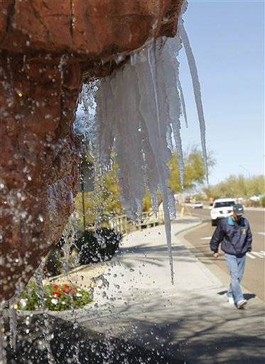 A spectator walks toward the TPC Scottsdale as icicles form on a water fountain at the Sheraton Desert Oasis Resort in Scottsdale, Ariz. The pro-am of the Phoenix Open golf tournament was called off due to frost.