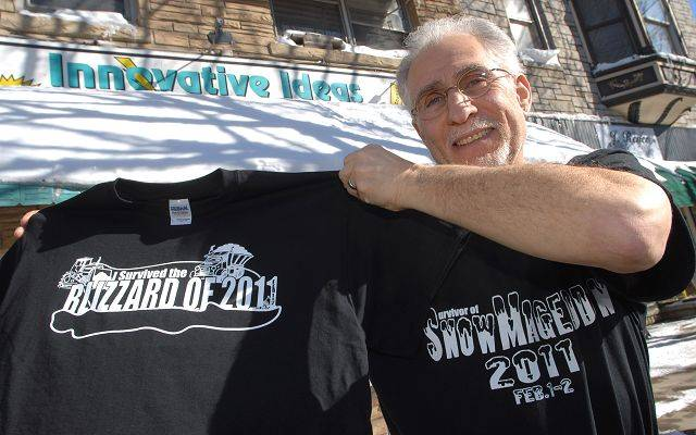 Antioch business owner Marc Mallen with two of his blizzard-related T-shirts he made.