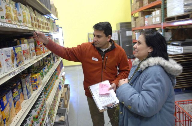 Volunteer Samir Khan, left, helps Memoza Skenderi of Naperville pick out her food items at the new Loaves and Fishes Community Pantry's distribution center and warehouse Saturday in Naperville.