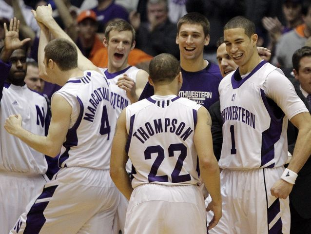 Northwestern players celebrate after they defeated Illinois 71-70 Saturday in Evanston. Northwestern led the entire game before Illinois tied it in the final minutes before losing.