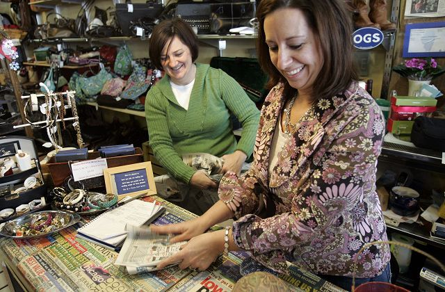 Co-owners Tricia Regan, left, and Erin Heard wrap up a sale. Since opening in September 2009, ReNew Family Consignment has exceeded expectations.
