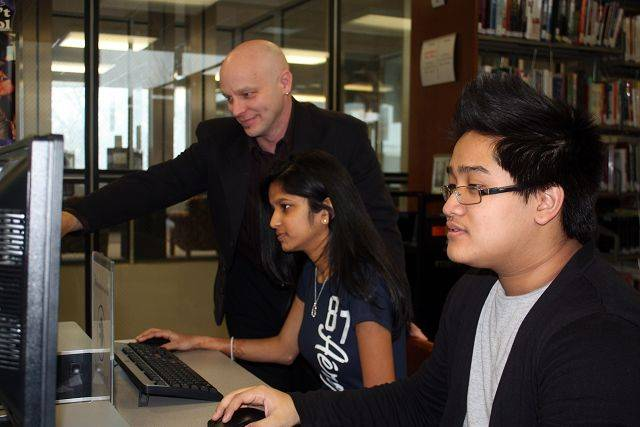 Maine West Technology Manager Neil Charlet, standing, with Parisha Patel and Jimmy Yim.