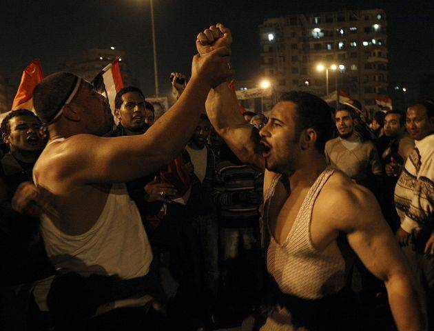 Two Egyptian men celebrate after President Hosni Mubarak resigned and handed power to the military at Tahrir square, in Cairo, Egypt, Friday, Feb. 11, 2011.