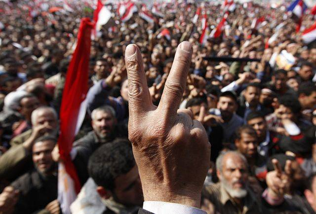 An anti-government protester flashes V sign at Tahrir square, in Cairo, Egypt, Friday, Feb. 11, 2011.