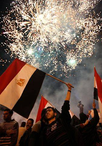 An Egyptian man carries his national flag as demonstrators set off fireworks during celebrations outside the Egyptian embassy in Beirut, Lebanon, Friday, Feb. 11, 2011.