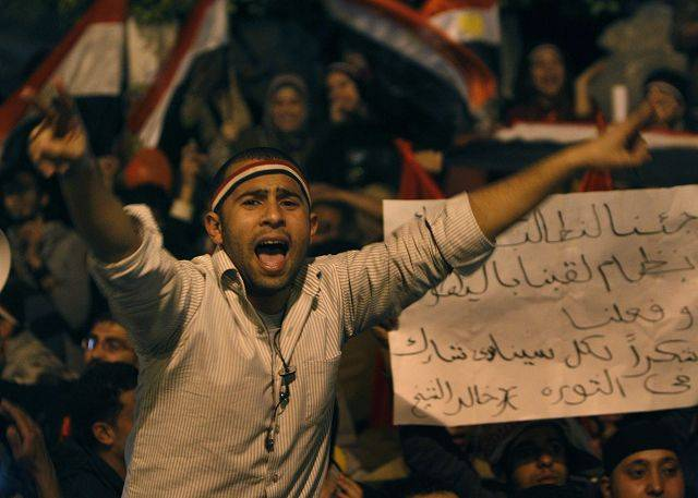 An Egyptian man, flashes the V sign as he celebrates after President Hosni Mubarak resigned and handed power to the military at Tahrir square, in Cairo, Egypt, Friday, Feb. 11, 2011.