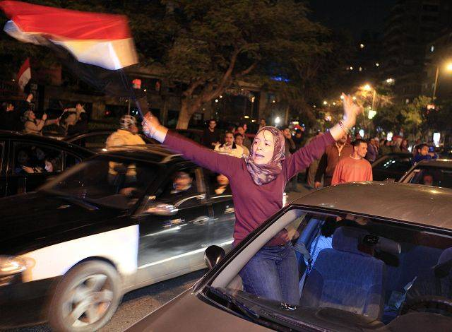 An Egyptian woman celebrates after President Hosni Mubarak resigned and handed power to the military in Cairo, Egypt, Friday, Feb. 11, 2011. Fireworks burst over Tahrir Square and Egypt exploded with joy and tears of relief after pro-democracy protesters brought down President Hosni Mubarak with a momentous march on his palaces and state TV.