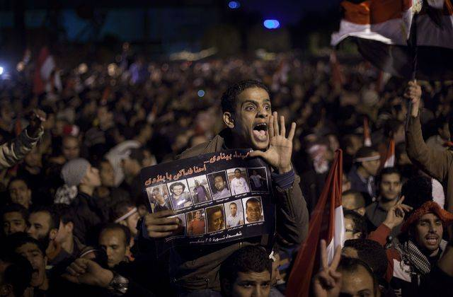 Anti-government protesters react as they watch on a big screen as Egyptian President Hosni Mubarak makes a televised statement to his nation in Tahrir Square in downtown Cairo, Egypt Thursday, Feb. 10, 2011.