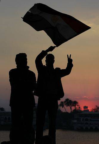 Anti-government protesters standing next to the Nile river wave an Egyptian flag and flash the victory sign at sunset, just before the news of the resignation of President Hosni Mubarak.