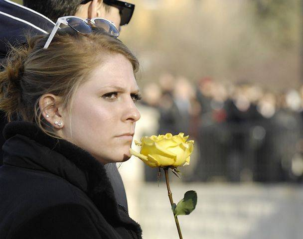 A family member holds a yellow rose as she listens to NIU President John G. Peters speak at a memorial service for the students killed there three years ago.