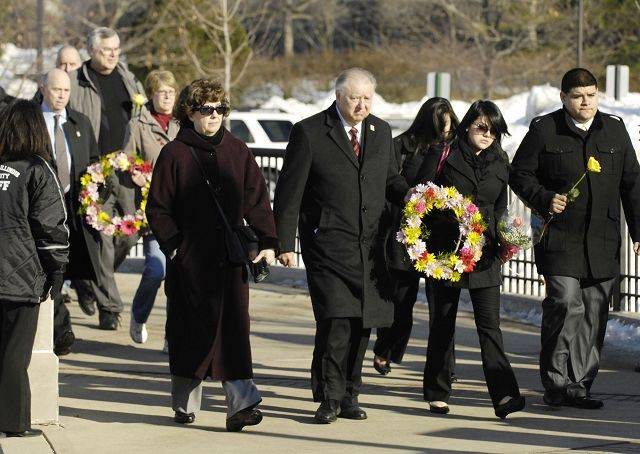 NIU President John G. Peters walks across campus Monday with families of the students killed at Northern Illinois University three years ago, to place a wreath at a memorial.