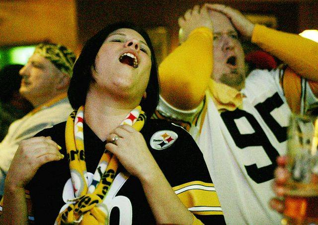Steelers fans Becky Rogers of DeKalb and Tom Burns of Naperville cheer for their team Sunday night at Mullen's Bar and Grill Sunday in Lisle.