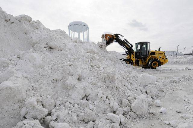 "Snow plowed from the streets, commuter lots, parking lots, and cul-de-sacs of Wheaton is being piled up at the county fairgrounds. Kevin Sheehan, from the Wheaton Public Works Department is putting the collected snow into even higher piles to make room for more. Asked how much snow is here, Sheehan said laughing, ""tons and tons and tons."""