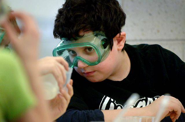 Copeland Manor fifth graders conducted chemistry experiments with parent volunteers during the Kids and Chemistry program Thursday in Libertyville. Student Mason Maniloff keeps a sharp eye as his partner works with a solution during an experiment.