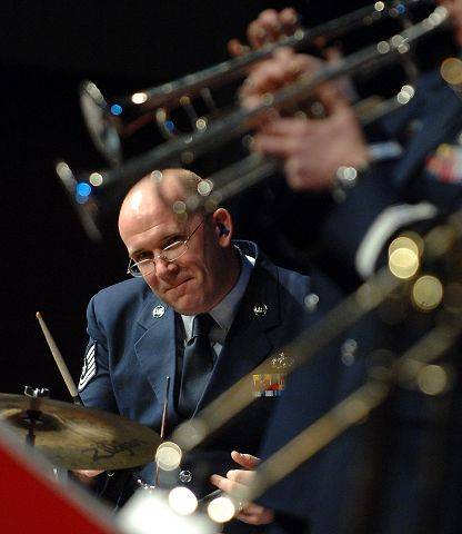 Technical Sergeant Paul Shaw mans the drums during a concert by the United States Air Force Shades of Blue Jazz Ensemble at Geneva High School Thursday evening.