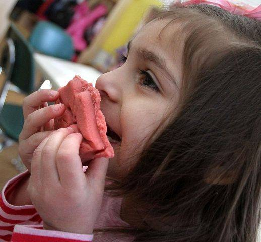District 220 preschooler Alexia Torres makes a face using clay cutout lips during a series of festive Valentine's Day activities with Barrington High School Code Red students at the Early Learning Center in Barrington on Thursday.