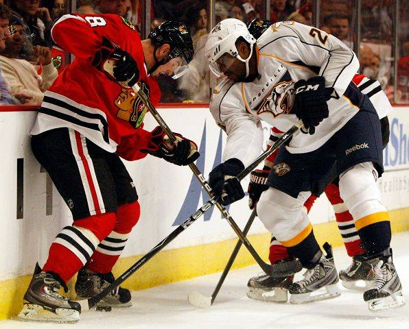 Nashville Predators' Joel Ward, right, and the Blackhawks' Nick Leddy battle for the puck earlier this season.