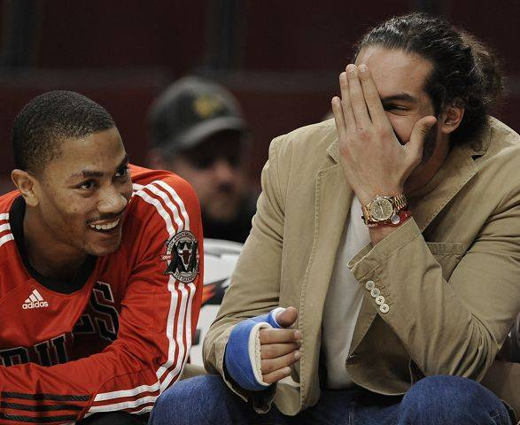 Derrick Rose, left, jokes with center Joakim Noah, who has been sidelined since undergoing thumb surgery on Dec. 16.