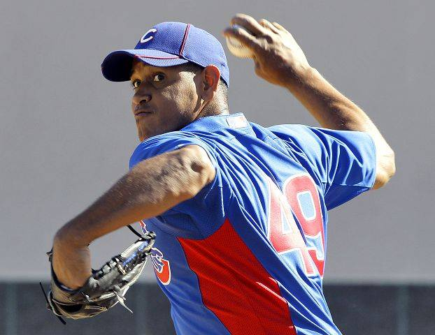 Chicago Cubs pitcher Carlos Marmol pitches, Monday, Feb. 14, 2011, during team workouts at the Cubs' baseball spring training facility in Mesa, Ariz.