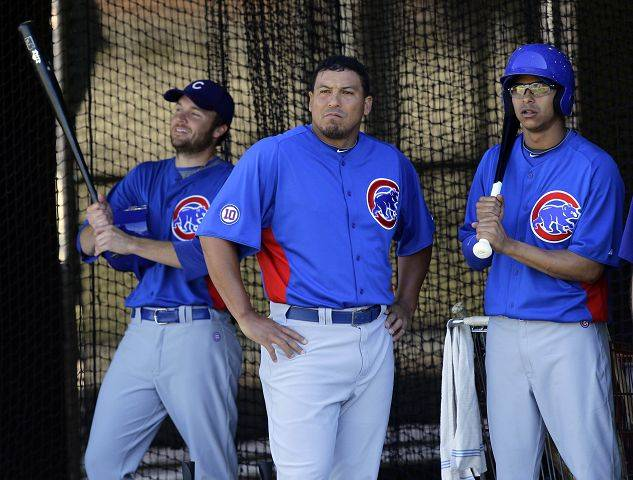 Chicago Cubs pitcher Carlos Zambrano, center, pitcher Angel Guzman, right, and pitcher Jeff Stevens watch their teammates, Monday, Feb. 14, 2011, during team workouts at the Cubs' baseball spring training facility in Mesa, Ariz.