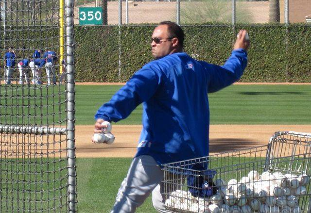 Bench coach Pat Listach tosses batting practice balls to hitters during workouts Tuesday at Cubs camp in Mesa, Ariz.