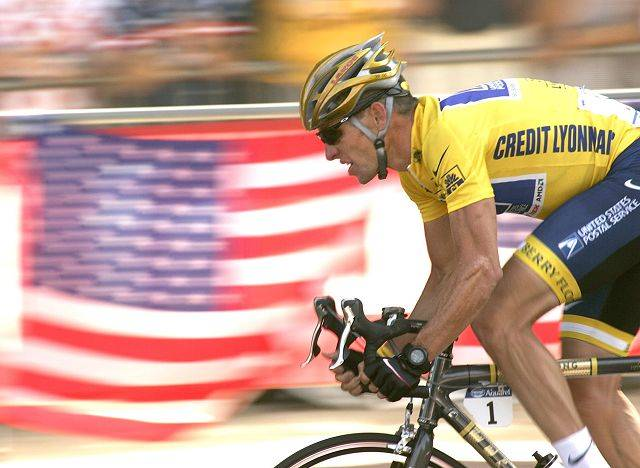 Lance Armstrong rides down the Champs Elysees avenue past U.S. flags in 2004 during the 20th and last stage of the Tour de France cycling race between Montereau, southeast of Paris, and the Champs-Elysees in Paris.