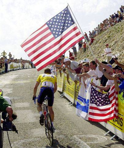 Overall leader Lance Armstrong, of Austin, Texas, foreground, in action as he climbs Mont Ventoux, urged by supporters waving U.S. flags, during the 14th stage of the Tour de France cycling race between Lodeve and Le Mont Ventoux, southern France, Sunday July 21, 2002. Richard Virenque, of France, won the stage and Armstrong finished in third place retaining the yellow jersey.