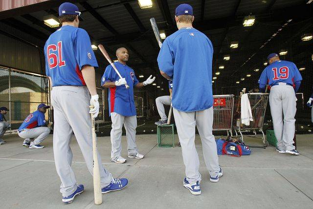 Chicago Cubs' Marlon Byrd, middle facing, talks with teammates Matt Rizzotti, right, and Josh Vitters, as Bobby Scales (19) and Marquez Smith, far left, wait their turn for batting practice during baseball spring training Wednesday, Feb. 16, 2011, in Mesa, Ariz. Byrd, the Cubs center fielder, reiterated his trust in BALCO founder Victor Conte and said that's why he's still working with a man who served jail time for steroids distribution.