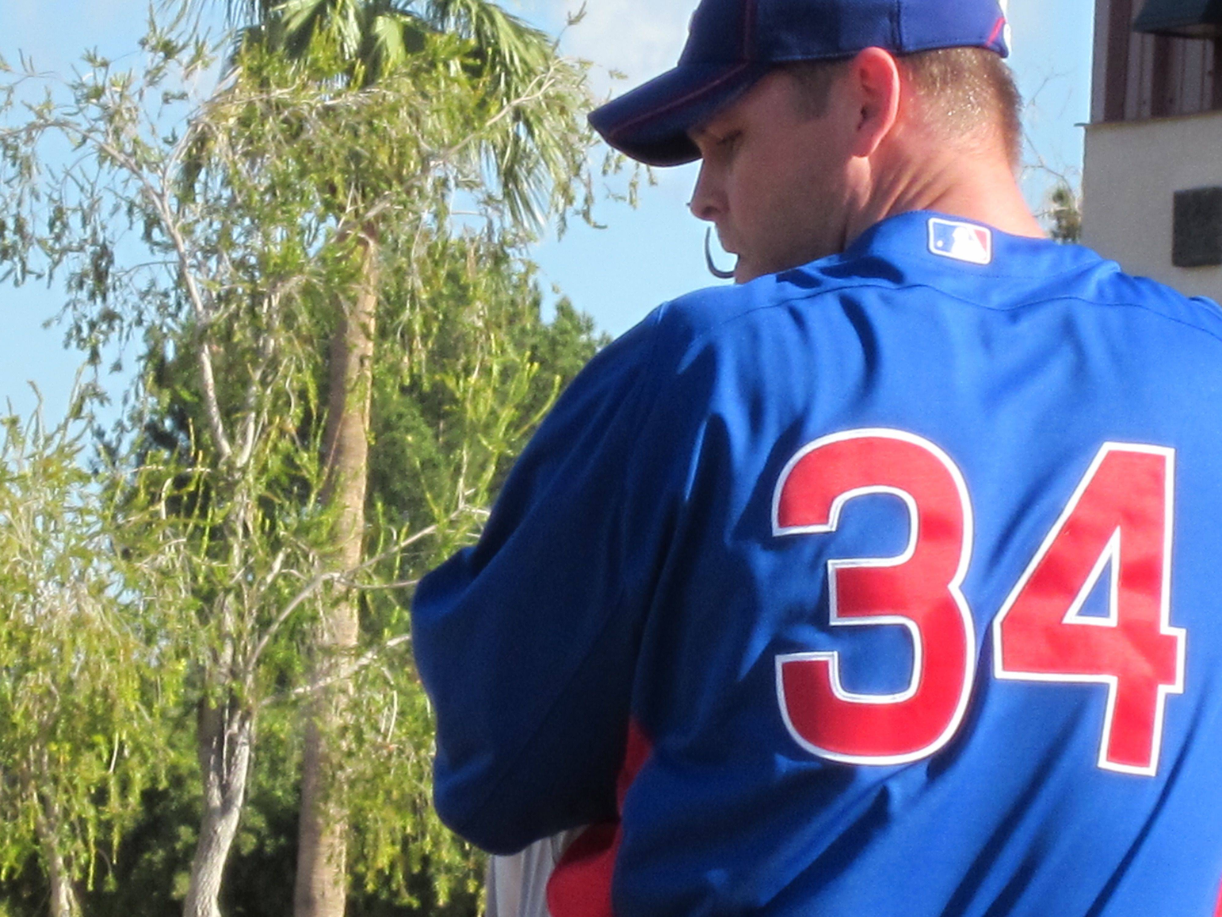 Images from Cubs players and personnel at spring training in Mesa on Thursday. Kerry Wood prepares to wind up.