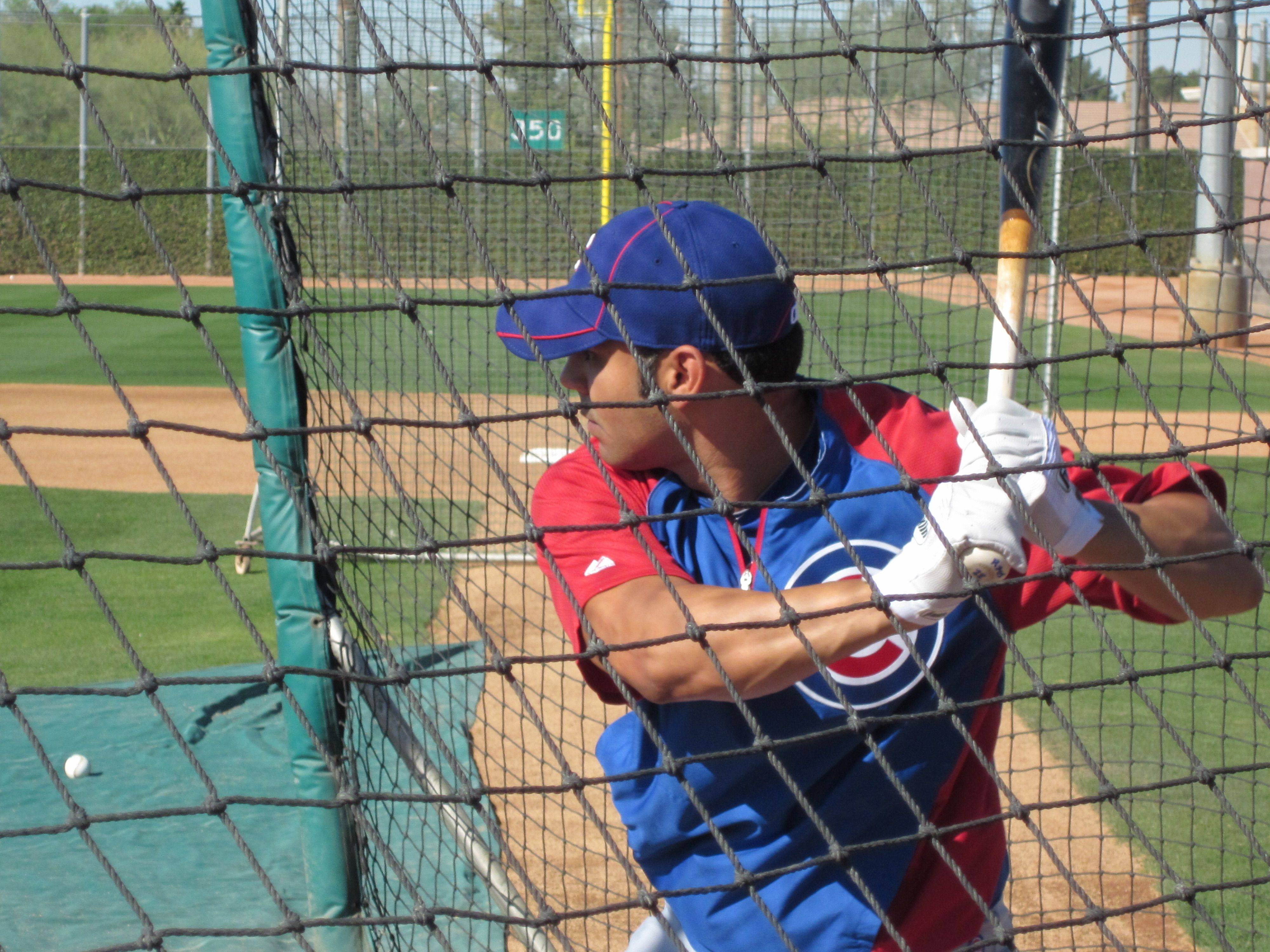 Images from Cubs players and personnel at spring training in Mesa on Thursday. 3B nonroster man Scott Moore awaiting a pitch in the cage