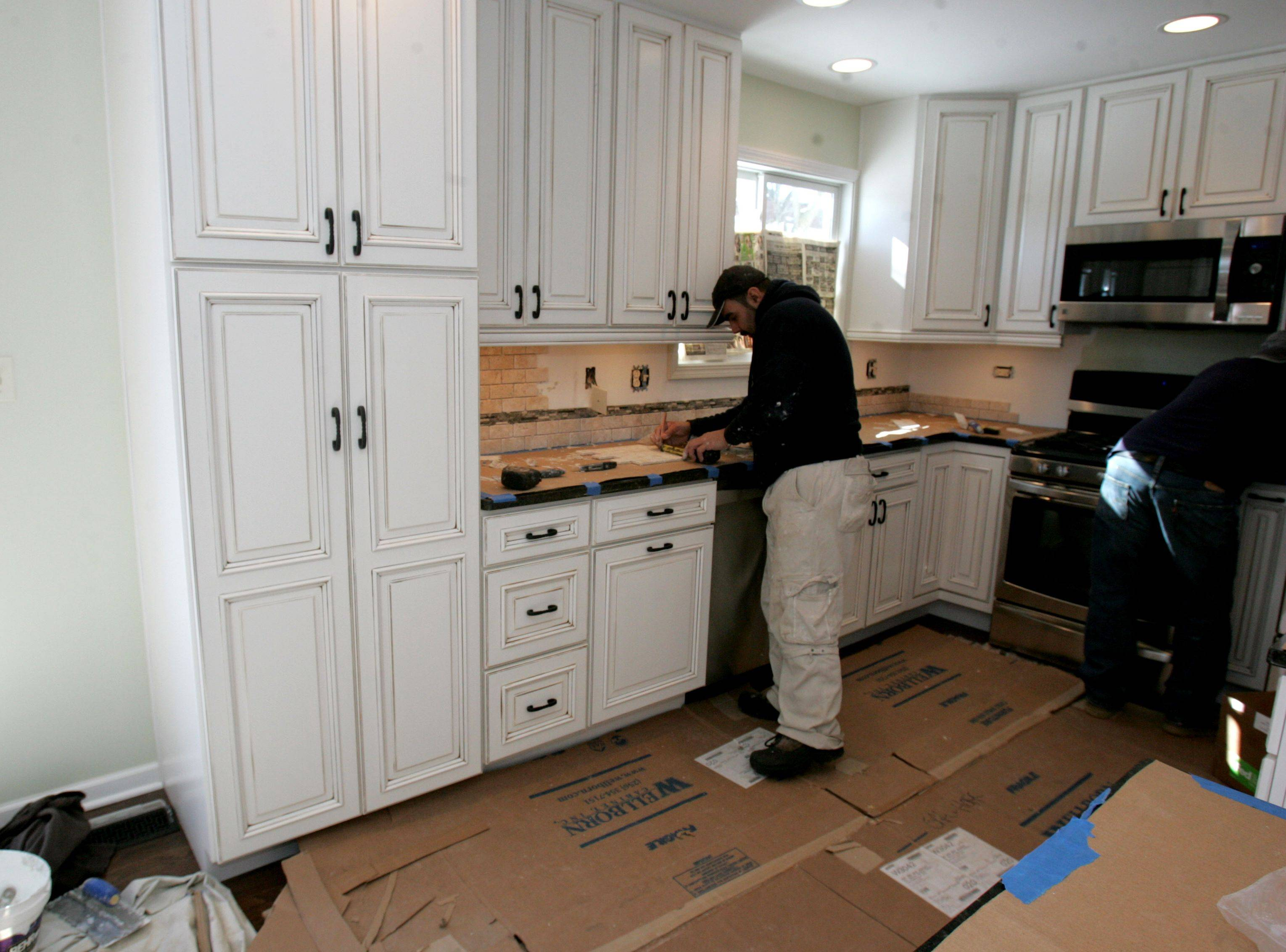 Workers put up backsplash in Pat Hoffman's kitchen in Woodridge.