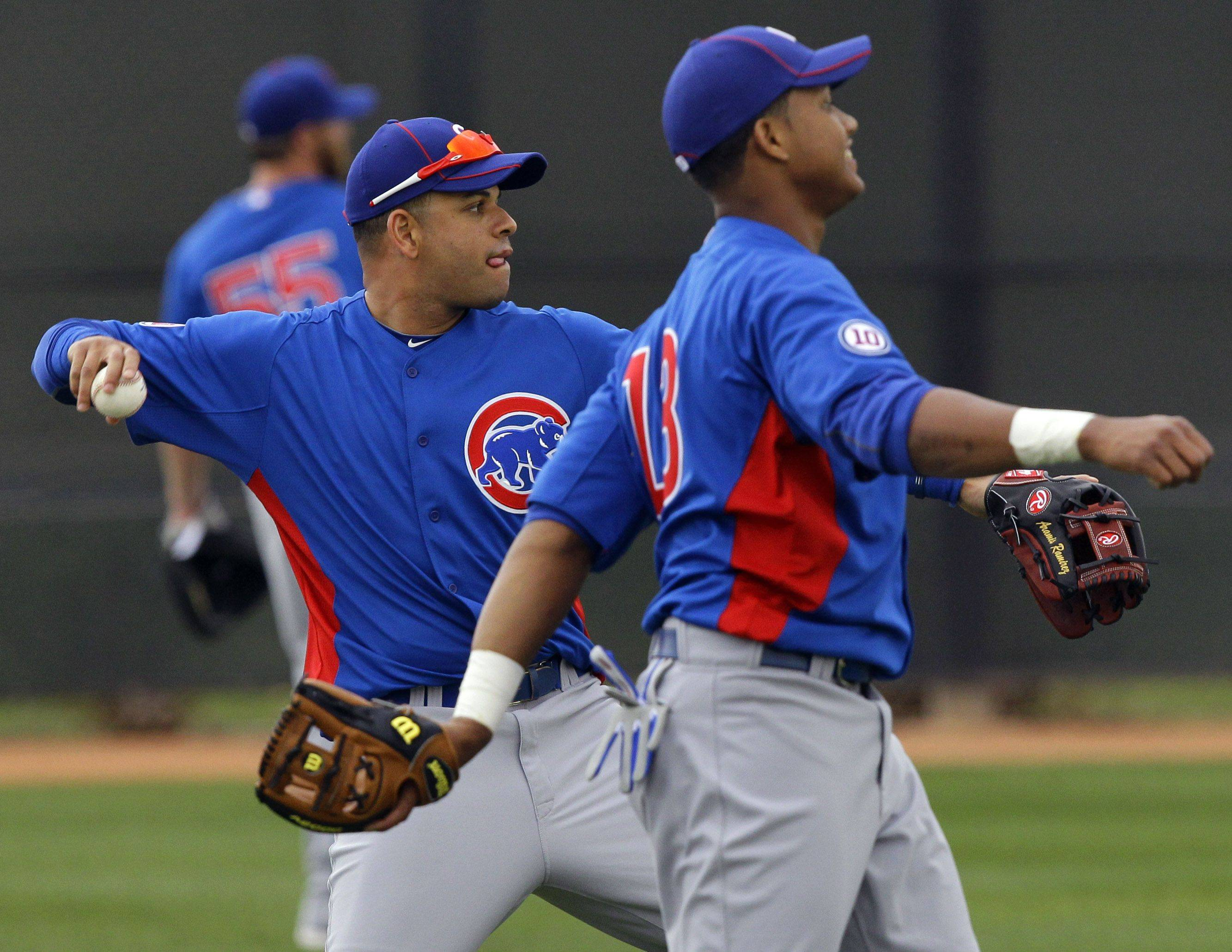 Chicago Cubs third baseman Aramis Ramirez, left, and Starlin Castro throw, Saturday, Feb. 19, 2011, at the Cubs' baseball spring training facility in Mesa, Ariz.