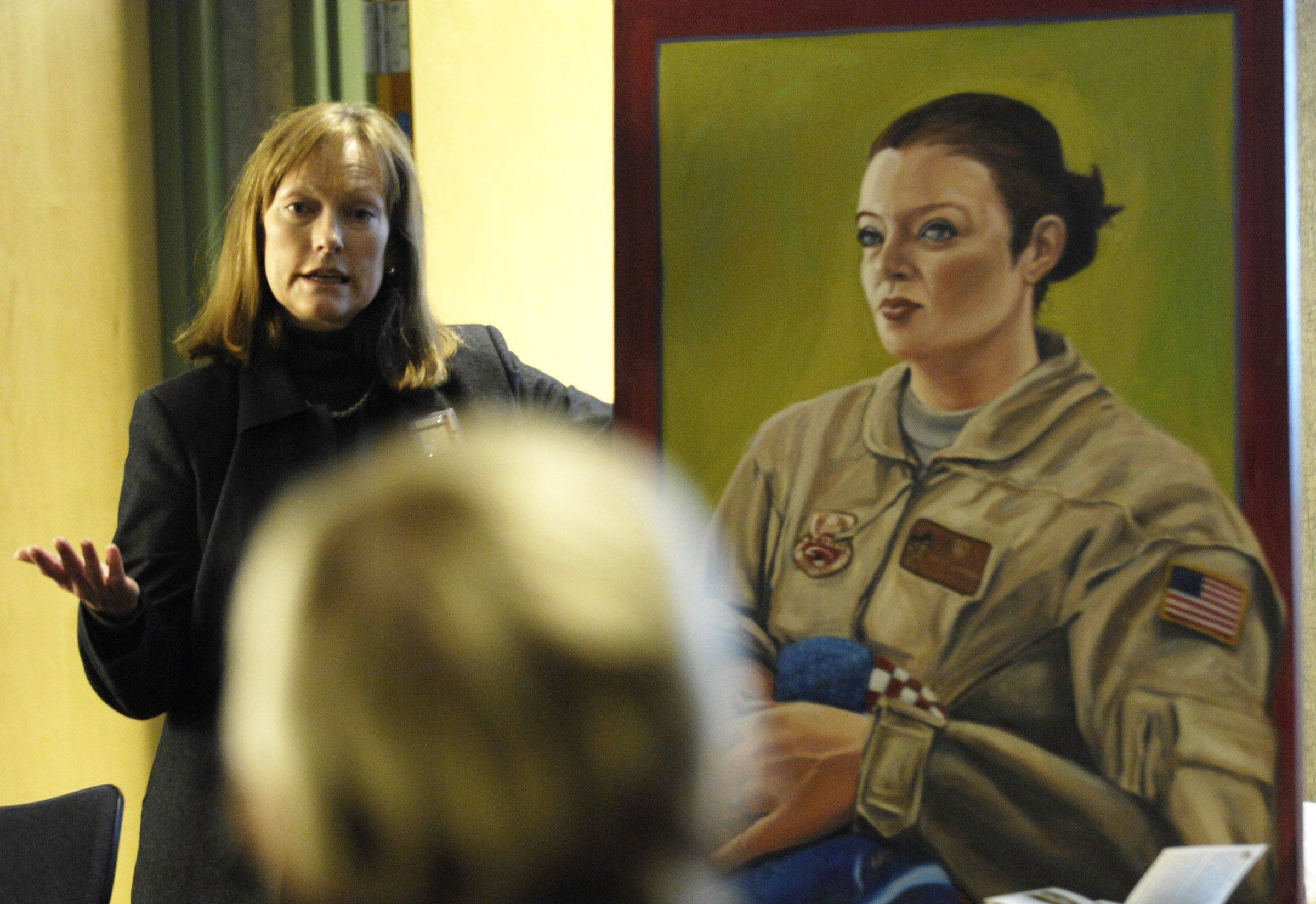 "Artist Jeanine Hill-Soldner speaks about her paintings of local veterans Sunday at the Algonquin Area Public Library. ""Portraits of American Veterans: A Continuing Dialogue"" will be on display there for the rest of the month. Each of the oil on canvas paintings measures 30 by 40 inches."