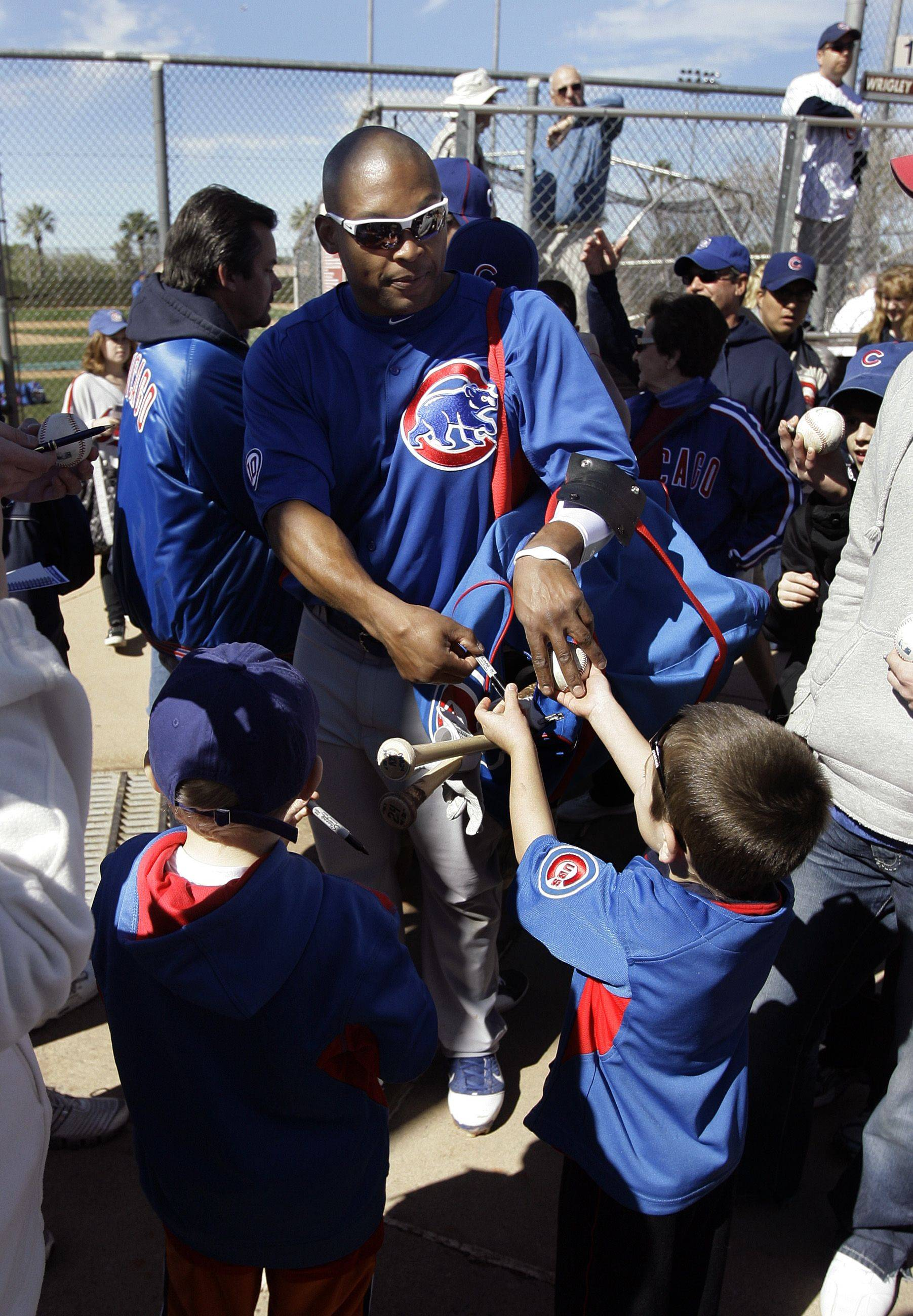 Chicago Cubs outfielder Marlon Byrd hands the autographed baseball he signed back to Tim Beverly, 4, of Framingham, Mass., following batting practice during baseball spring training Monday, Feb. 21, 2011, in Mesa, Ariz.