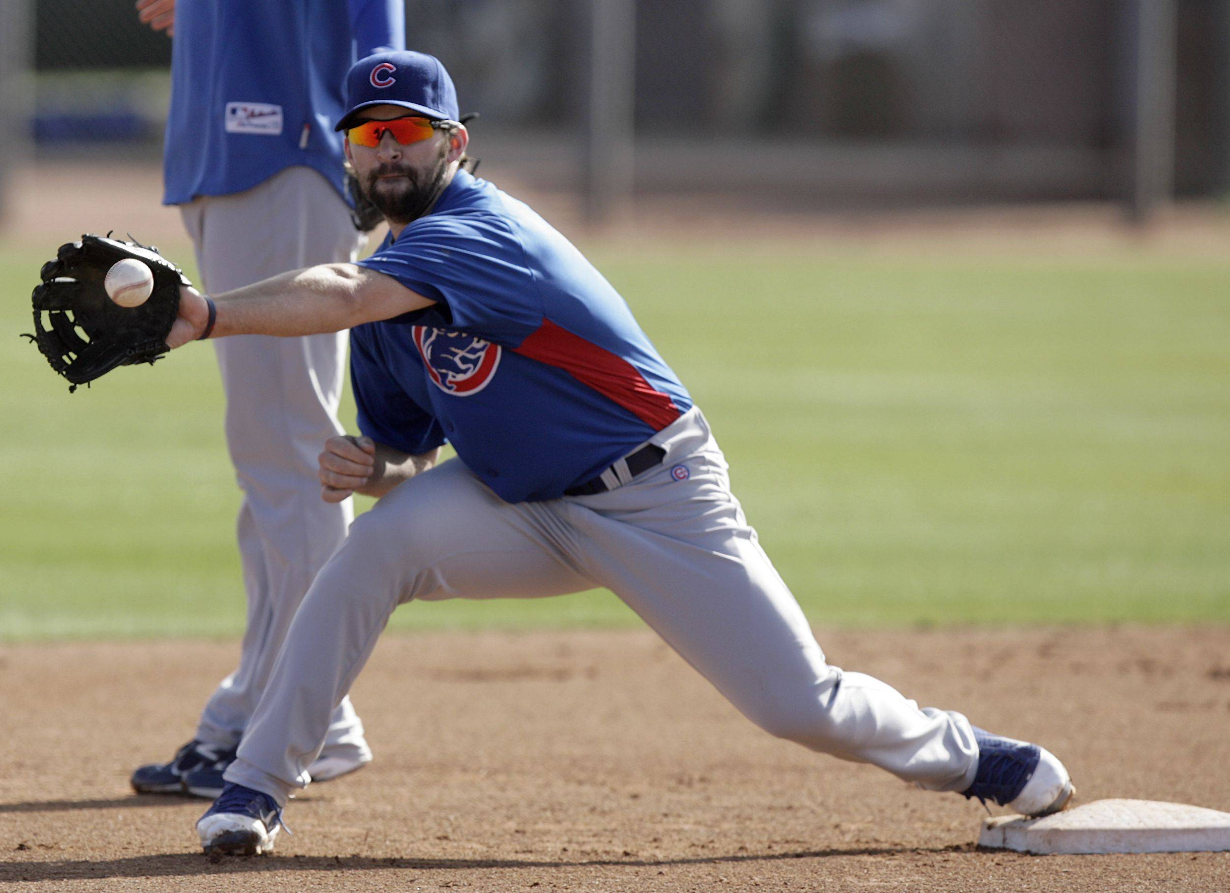 Chicago Cubs infielder Blake DeWitt stretches to make a catch while covering a base during baseball spring training Monday, Feb. 21, 2011, in Mesa, Ariz.