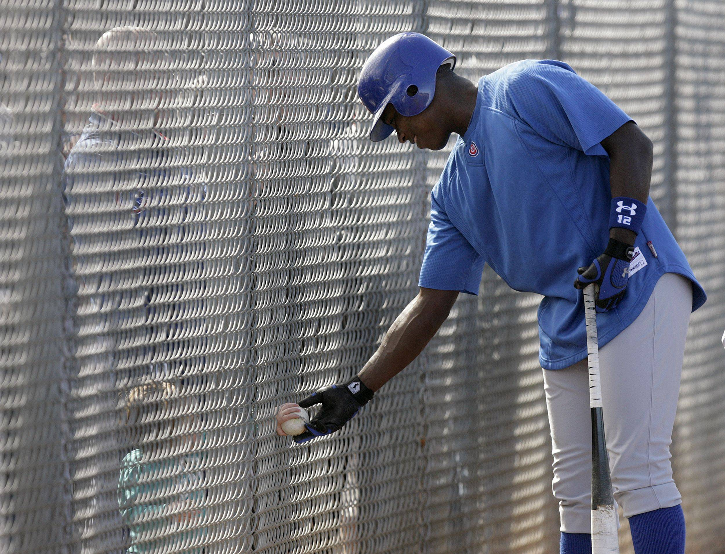 Chicago Cubs outfielder Alfonso Soriano passes a baseball through a fence to a young fan as he prepares to take batting practice during spring training Monday, Feb. 21, 2011, in Mesa, Ariz.
