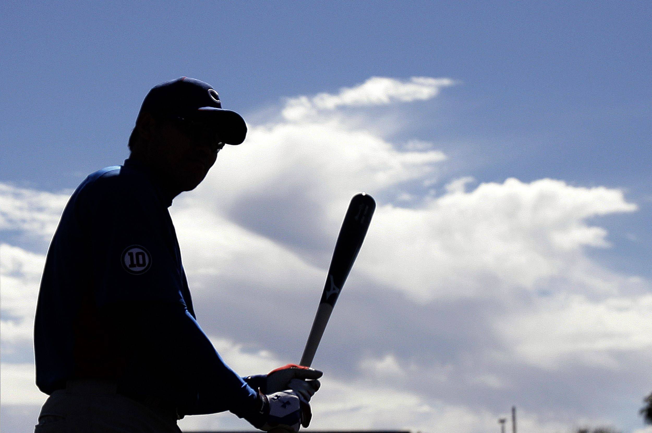 Chicago Cubs outfielder Kosuke Fukudome, of Japan, swings a bat under clearing skies following two days of rain, during baseball spring training Monday, Feb. 21, 2011, in Mesa, Ariz.