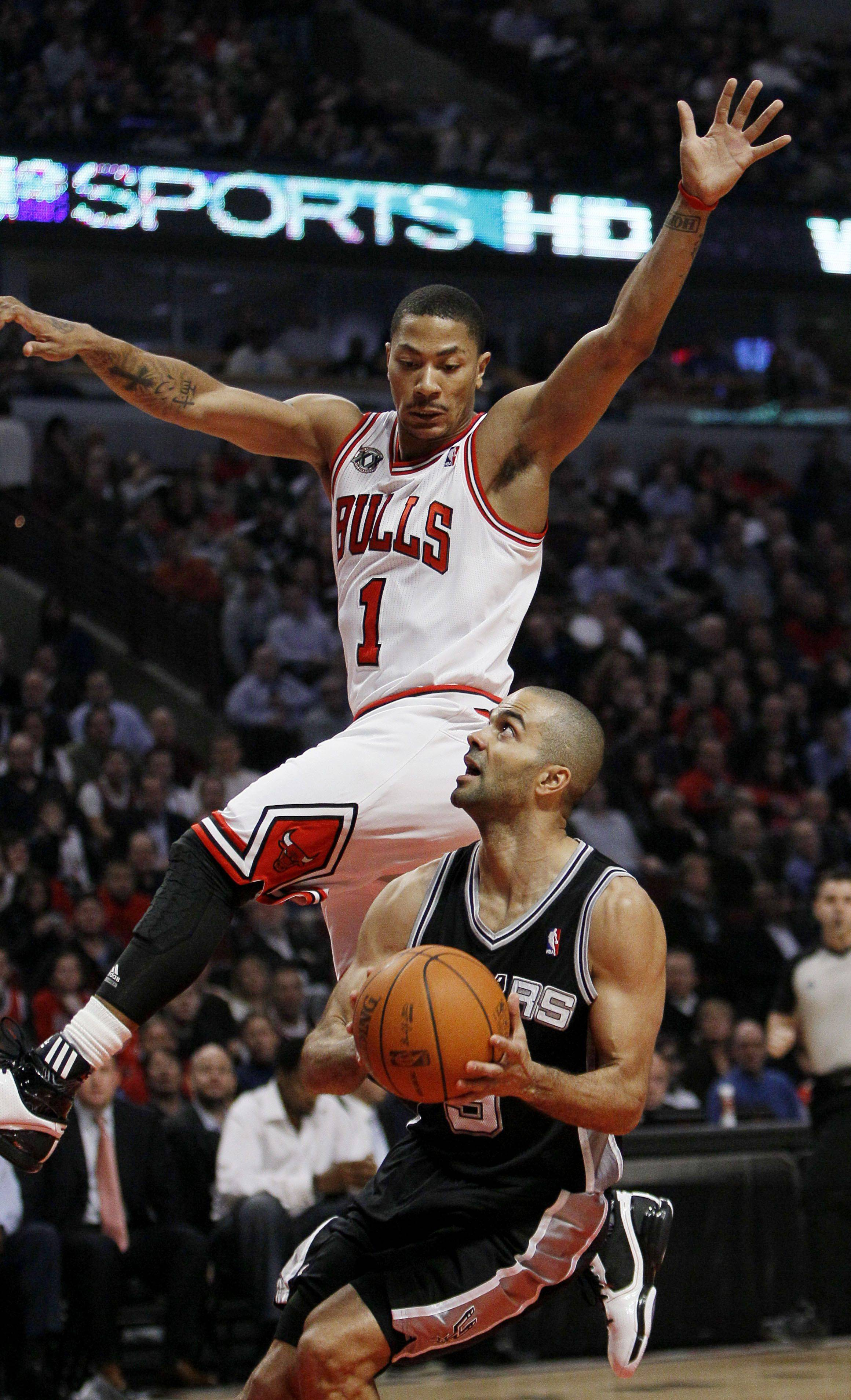 San Antonio Spurs guard Tony Parker, bottom, gets Chicago Bulls guard Derrick Rose off his feet during the first half of Thursday's game.