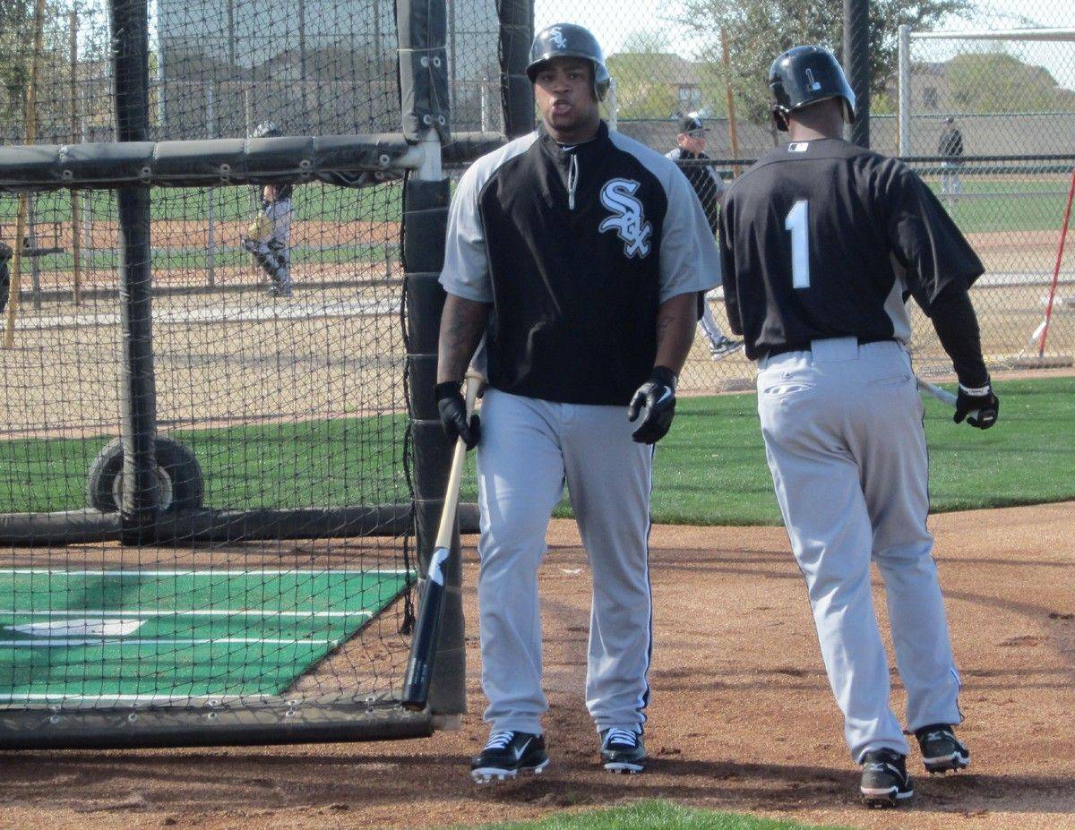 Dayan Viciedo and Juan Pierre (1) trade places in the batting cage Monday during workouts at the White Sox training facilities in Glendale, Ariz.