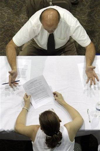 A job applicant receives advice on his resume while attending a job fair in Southfield, Mich.