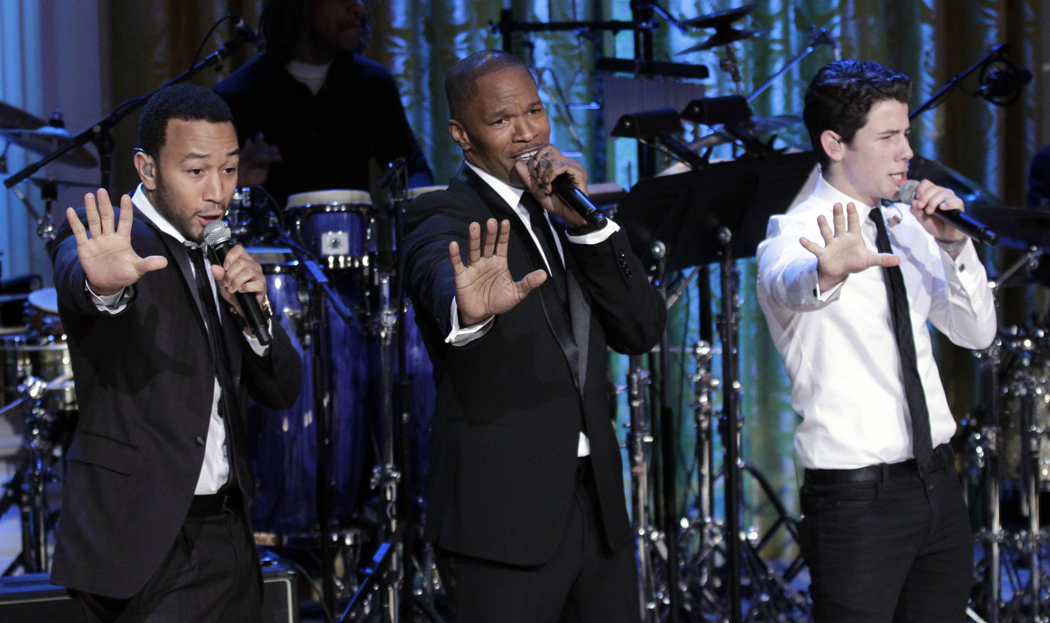 From left, singers John Legend, Jamie Foxx, and Nick Jonas, perform on stage during the White House Music Series saluting Motown in the East Room of the White House in Washington, Thursday.