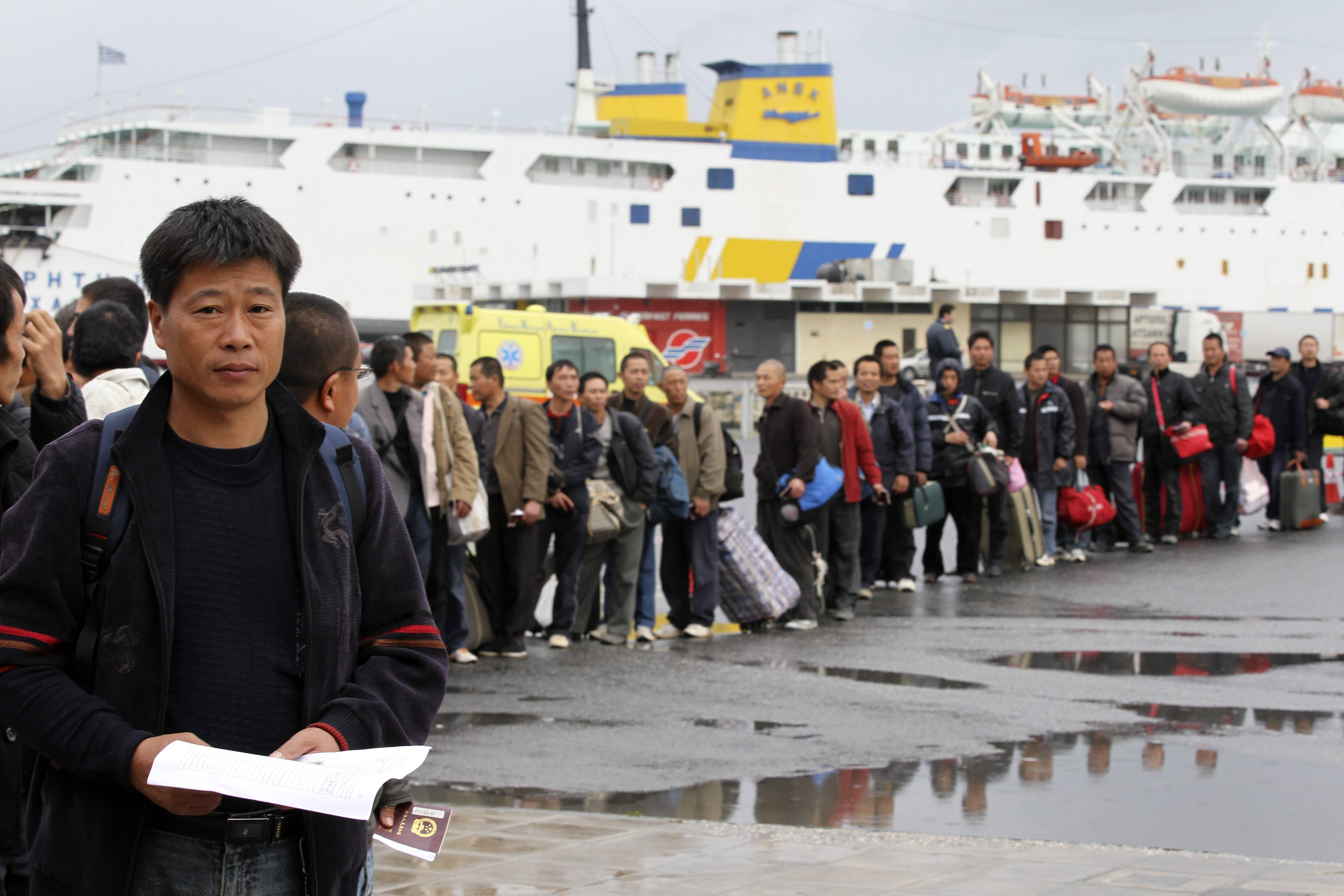 Chinese evacuees wait in a lane to pass the passport control at the port of Iraklio city, on the Greek island of Crete, Thursday.