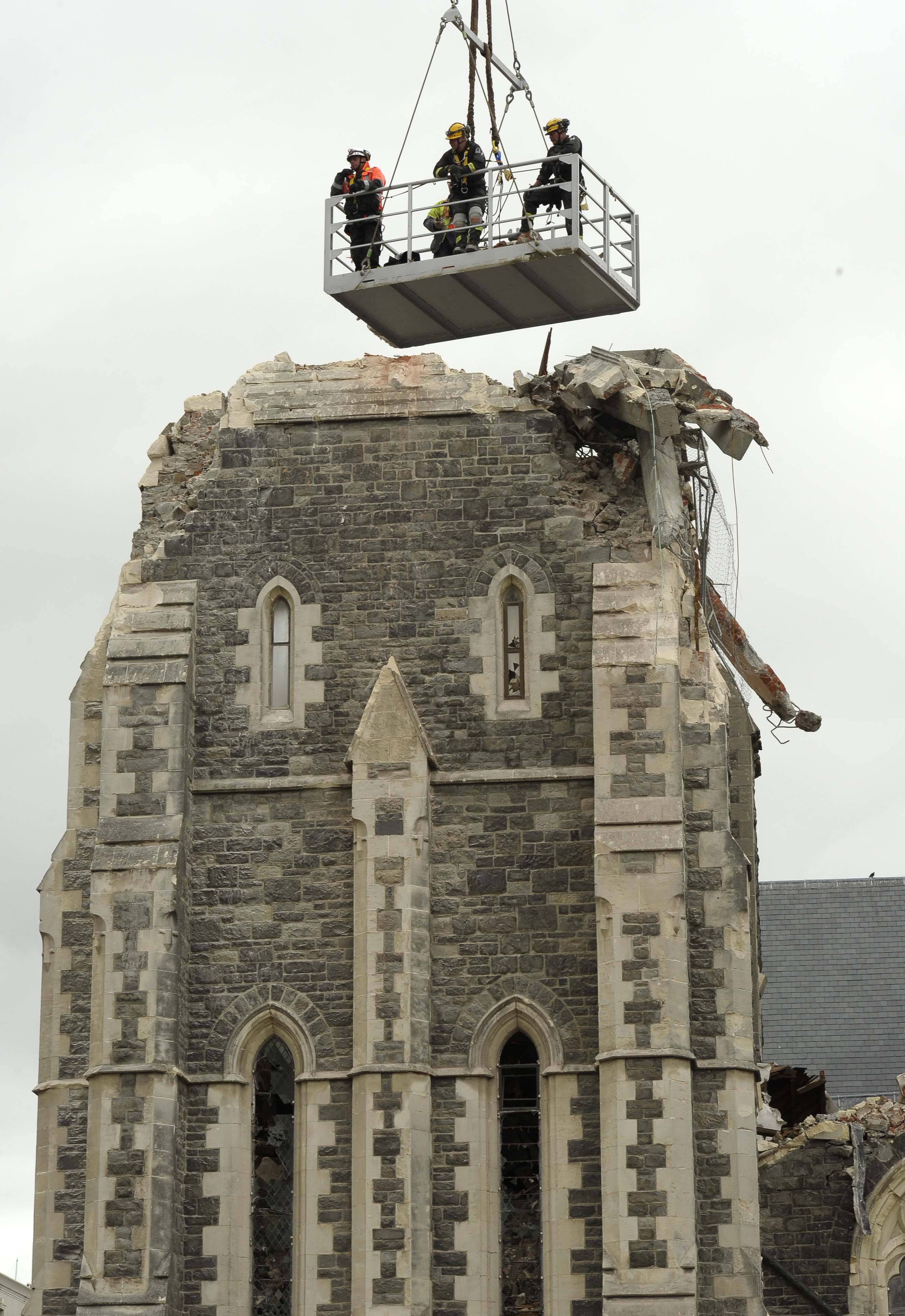 Recovery operation workers are lowered by crane onto the top of the Christchurch Cathedral in Christchurch, New Zealand, Friday.