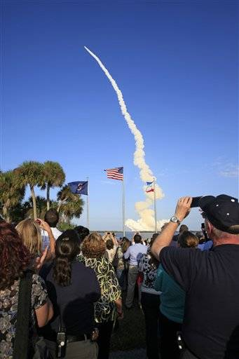 Spectators watch and take photos of space shuttle Discovery as it lifts off from the Kennedy Space Center in Cape Canaveral, Fla., Thursday.