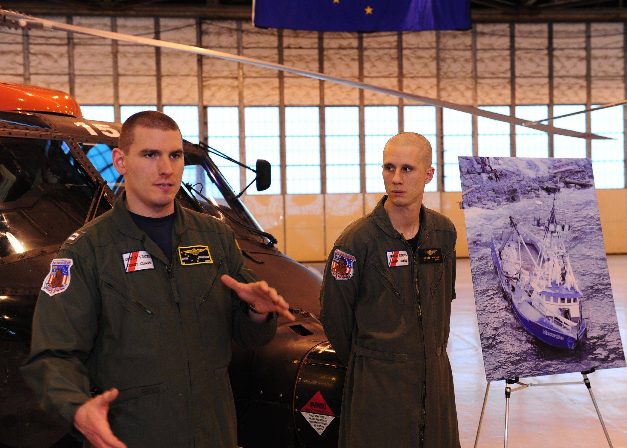 Lt. Mark Heussner, left, a Wheeling native and a Coast Guard helicopter pilot, describes his participation in the rescue of Alaskan fishermen on the Midnite Sun. At right is Petty Officer 3rd Class Michael Wallace.