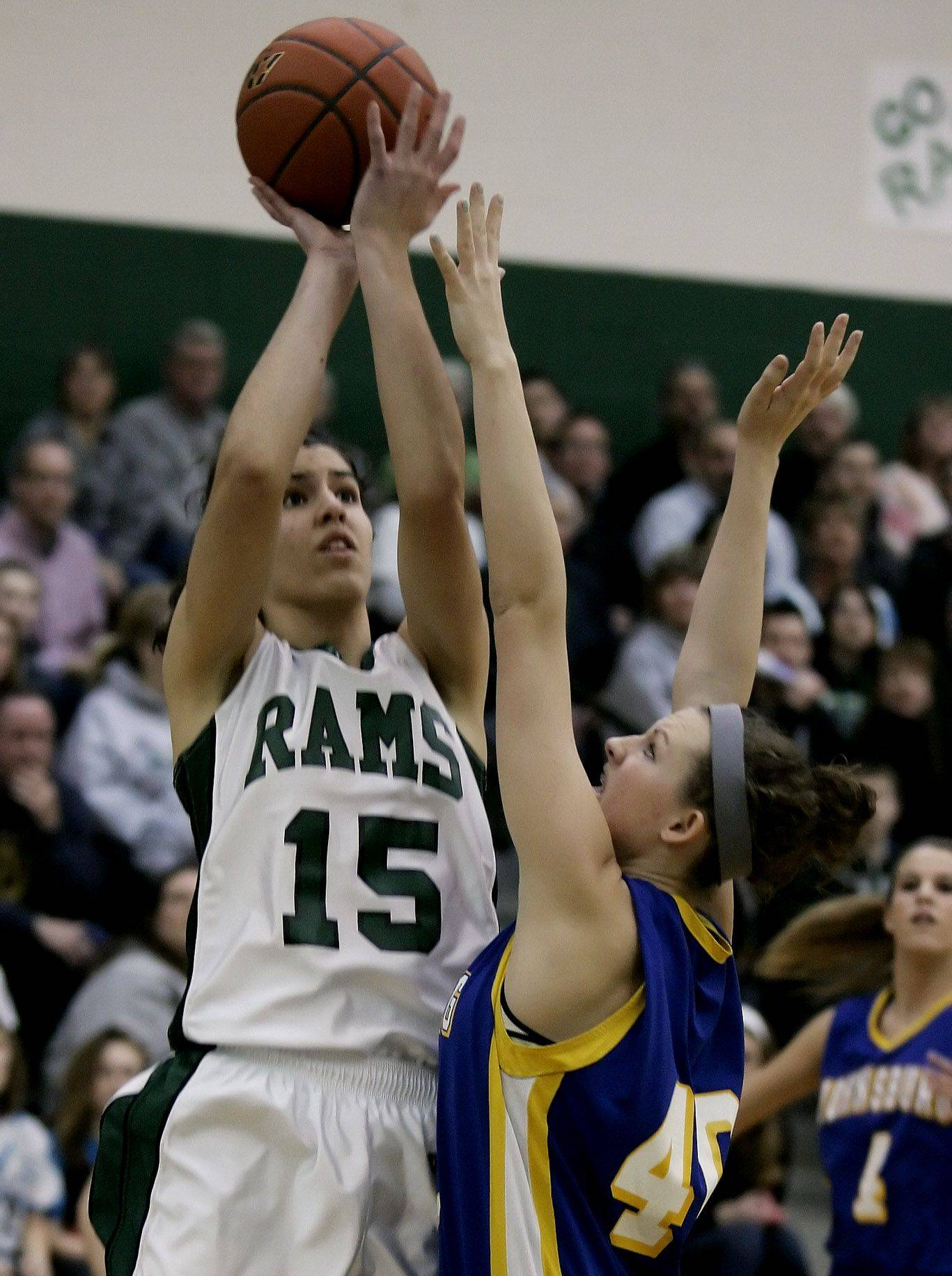 Grayslake Central's Rebekah Llorens, who poured in 37 points and grabbed 20 rebounds, skies for a shot over Johnsburg defender Ashley Schuld during the Class 3A girls sectional final Thursday at Grayslake Central.