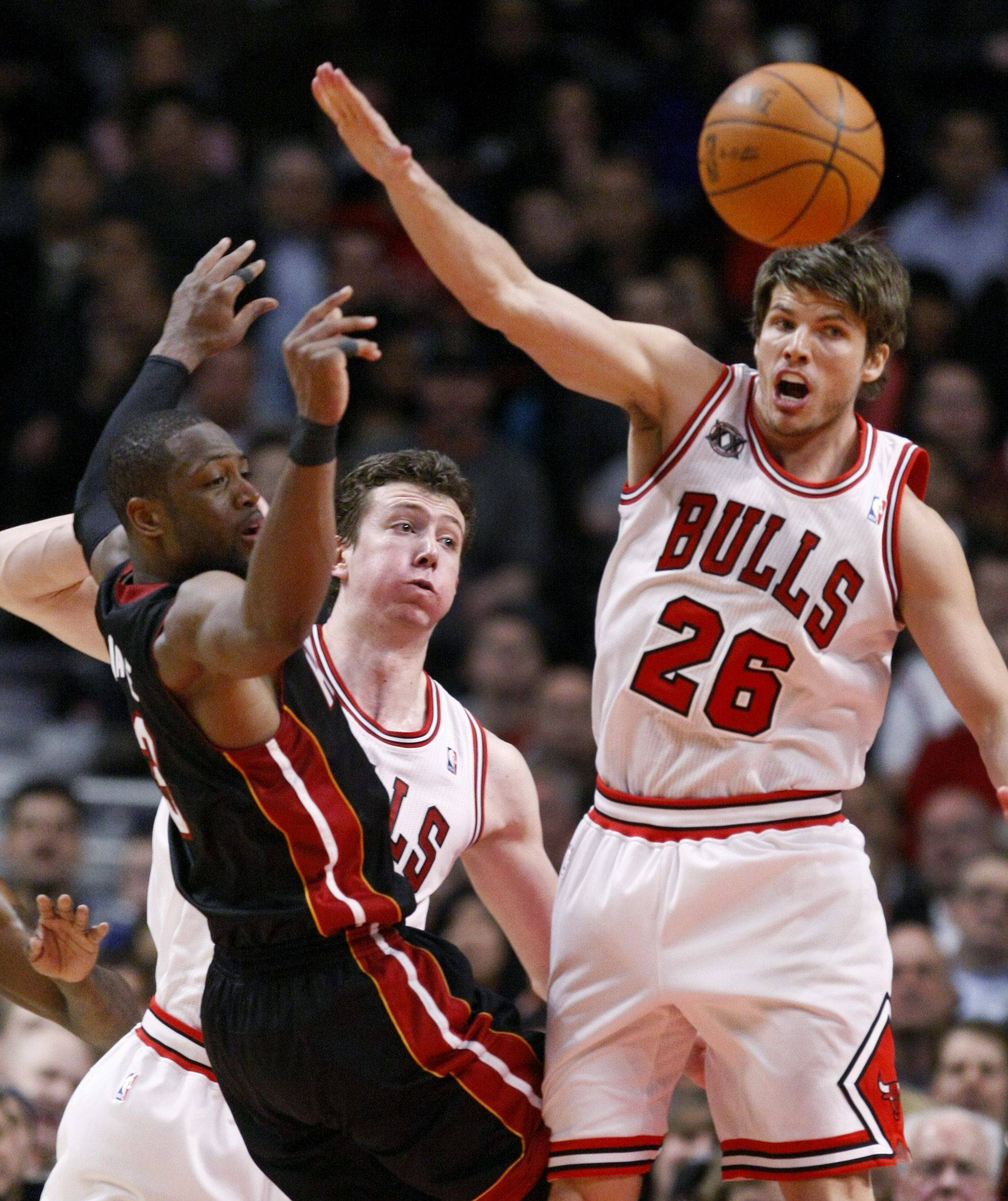 Miami Heat shooting guard Dwyane Wade, left, is forced to pass by the defense of Chicago Bulls center Omer Asik, center, and Kyle Korver, during the second half of an NBA basketball game Thursday, Feb. 24, 2011, in Chicago. The Bulls won 93-89.