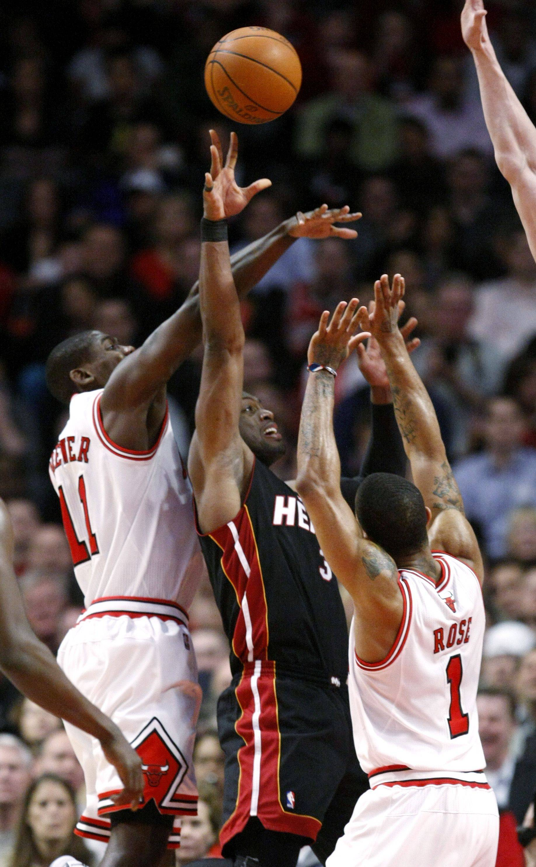 Miami Heat guard Dwyane Wade, center, puts up a shot between Chicago Bulls' Ronnie Brewer, left, and Derrick Rose, during the second half of an NBA basketball game Thursday, Feb. 24, 2011, in Chicago. The Bulls won 93-89.